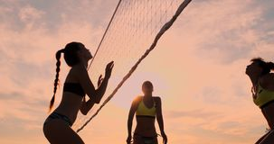SLOW MOTION, LOW ANGLE, CLOSE UP, SUN FLARE: Athletic girl playing beach volleyball jumps in the air and strikes the. Ball over the net on a beautiful summer stock footage