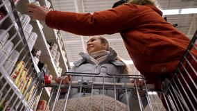 Slow motion low angle shot couple walks chooses products. Slow motion low angle shot couple walks along supermarket rows with tinned food and chooses products stock video footage