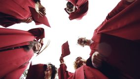 Slow motion low angle shot of graduates standing in circle throwing mortar-boards in the sky and laughing. Togetherness. Slow motion low angle shot of emotional stock footage
