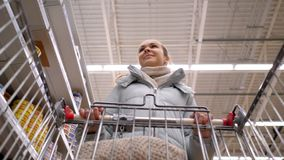 Slow motion low angle shot girl with cart walks past shelves. Slow motion low angle shot girl pushing shopping cart walks along supermarket shelf rows with stock footage