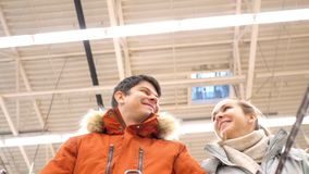 Slow motion low angle shot happy couple walks in store. Slow motion low angle shot happy couple with cart walks and talks smiling in large modern supermarket stock footage