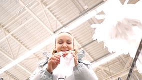 Slow motion low angle shot woman puts on disposable glove. Slow motion low angle shot woman puts disposable glove on hand against high ceiling in supermarket stock footage
