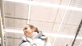 Slow motion low angle shot woman walks along store shelves. Slow motion low angle shot woman walks along shelves with products and looks at fresh goods in stock video footage