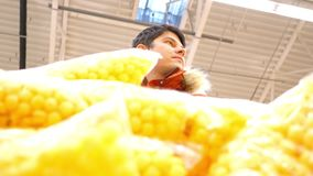 Slow motion low angle shot man fills cart with corn balls. Slow motion low angle shot young man in red jacket fills cart with sweet corn balls from supermarket stock footage