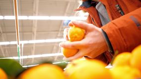 Slow motion low angle shot young man takes tangerines. Slow motion low angle shot young man in red jacket takes fresh aromatic tangerines in supermarket stock video