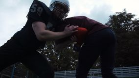 Two American football players hitting each other. Slow motion low-angle side view of two American football players hitting each other by accident during match stock video footage