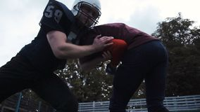 Two American football players hitting each other. Slow motion low-angle side view of two American football players hitting each other by accident during match stock footage