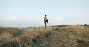 Slow Motion Male athlete exercising outdoors. Sports and active lifestyle. Man running into sunset, colorful sunset sky. stock footage