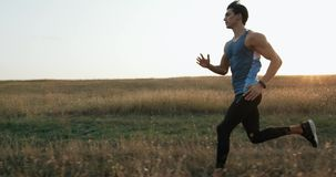 Slow Motion Male athlete exercising outdoors. Sports and active lifestyle. Male runner silhouette, Man running into stock video footage