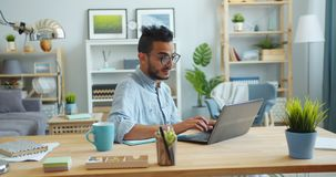 Slow motion of male freelancer using laptop at table in apartment typing. Slow motion of male freelancer Arabian guy in glasses using laptop at table in stock video footage