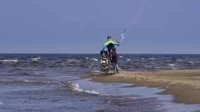 SLOW MOTION: A male kite surfer walks to the lake to start kite surfing.  stock video