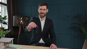 Slow motion of male`s midsection in formal jacket holding house keys in hand and showing to camera. Real-estate agent. Offering home keys to clients at table stock footage