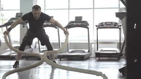 Slow motion of man with battle rope in functional training fitness gym stock video