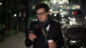Man holding a coffee walking in the evening smiling at the message stock footage