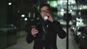 Man walking along the road at night holds a phone and taking a sip of coffee stock video