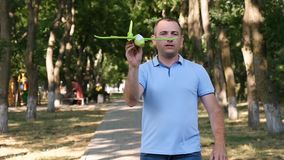 A man rests in a summer park, sweeping a toy plane in the wind recalling childhood. Slow motion. A man rests in a summer park, sweeping a toy plane in the wind stock footage