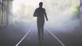 Slow motion man running away on train track. Back view. Abstract background shot. Concept of chasing the misty future. stock footage