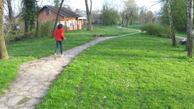 Slow motion of man running down the pathway in park. stock footage
