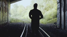 Slow motion. Man running forward on railway. Back view. Abstract silhouette shot. Concept of following your dreams. stock footage