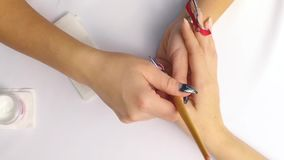 Slow Mo. The manicurist in the beauty salon applies a gel to the nail with a protective pattern. stock video footage