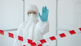 Slow motion of medic in suit and respirator stretching arm with stop gesture in infected quarantine area