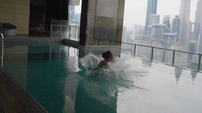 Girl Jumping into Swimming Pool. Slow motion medium shot of one girl jumping into beautiful rooftop swimming pool with lots of splashes stock video