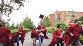 Slow motion of merry graduates running, holding diplomas and waving mortarboards enjoying freedom. Higher education stock video