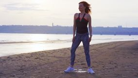 SLOW MOTION: A middle-aged woman with red hair does gymnastics on the sandy shore of a large river. stock footage