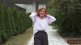 ec93191d701 SLOW MOTION: A Middle Aged Woman With Red Long Hair And A Pink Shirt ...