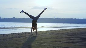 SLOW MOTION: A middle-aged woman with red hair and in sports uniform makes a somersault. A woman practices gymnastics on the sandy stock video