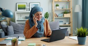 Slow motion of girl in hijab using laptop then talking on mobile phone at home. Slow motion of Middle Eastern girl in hijab using laptop then talking on mobile stock footage