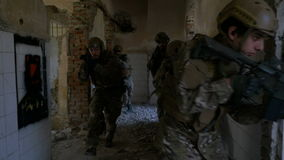 Slow motion of military soldiers running into a ruined building to practise maneuvers training stock video footage