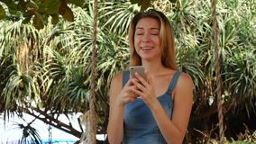 Slow motion model girl using Internet on smartphone relaxing in garden. Slow motion model female holding smartphone, young woman watching clothes in favorite stock footage