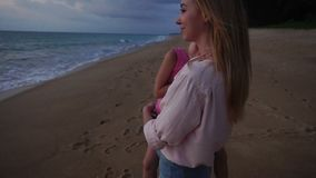 Slow motion mother lead daughter to see sunset at seaside stock video