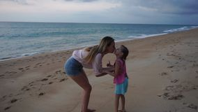 Slow motion mother and little daughter walking near sea in evening stock footage
