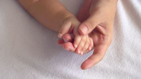 Slow motion of mother touching her baby hand. Softly between baby sleeping