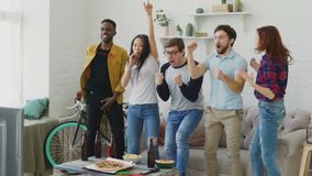 Slow motion of multi ethnic group of friends sports fans watching sport match on TV together jumping and cheering up new. Goal at home indoors stock footage