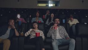 Slow motion of multiethnic group of students watching film in cinema eating. Slow motion of multiethnic group of students watching interesting film in cinema stock video