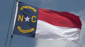 Slow Motion North Carolina Flag Blows in the Breeze. 8535 An extreme 180-fps slow motion establishing shot of the North Carolina state flag blowing in the breeze stock footage