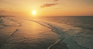 Slow motion of ocean waves at sun set light aerial view. Sunset wavy seascape at tropical paradise