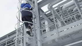 Slow Motion Oil Company Employee Climbs Ladder to Construction stock video footage