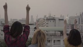 Slow motion - Outdoor shot of young people at rooftop party. Happy group of asian friends enjoy and play sparkler at roof top party at evening sunset. Holiday stock footage