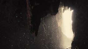 Slow motion panning shot of interior of tropical cave with drops falling.