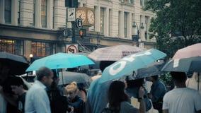 Slow motion pedestrians with umbrellas on Rainy Manhattan Crosswalk. New York City - circa October, 2017 - Pedestrians with umbrellas cross a rainy Manhattan stock video