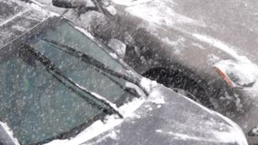 Slow motion of people cleaning snow and ice off her car wind shield window. On cold blizzard snow winter day stock video