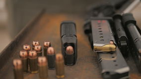 Slow Motion Person Picks Up and Puts Down Handgun Near Stash of Ammunition. Slow motion handheld shot of a stash of ammo. In the background a person picks up and stock video