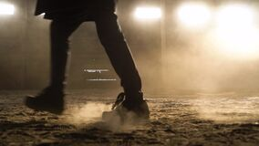 Slow motion. Person`s foot steps in front of the camera and leaves dusty footprints. Close-up of confident walking along