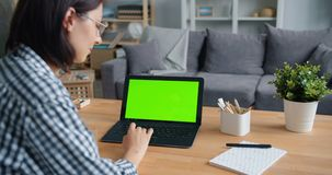 Slow motion of person using laptop computer with green mock-up screen at home. Slow motion of person young woman using laptop computer with green mock-up screen stock video