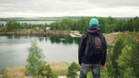 Slow motion portrait of active young man traveller with knapsack walking down the mountain and watching great view of. Lakes and forests and cloudy sky from stock footage