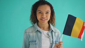 Slow motion portrait of African American woman waving flag of Germany smiling. Looking at camera on light blue background. Patriotism and youth concept stock video